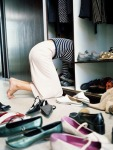 photo of Woman on knees searching through shoes in wardrobe