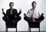 image of a man and a woman wearing suits seated in meditative pose on chairs