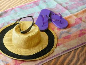 image of beach blanket with hat, sunglasses and sandals on it
