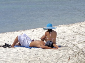 image of a couple laying on the beach